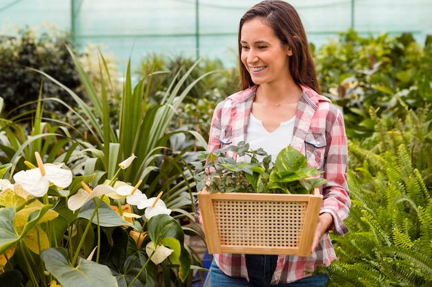 Portrait of woman carrying basket in greenhouse