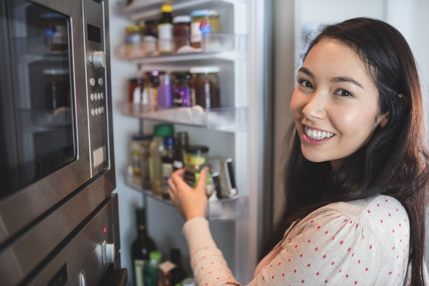 Portrait of woman checking her refrigerator