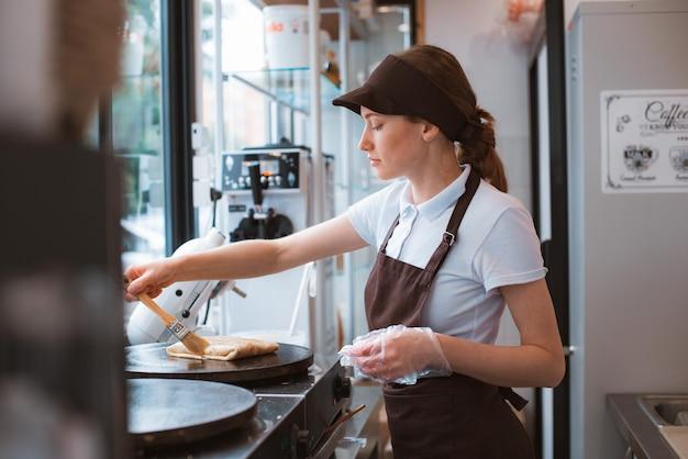 Шеф-повар женщины портрета выпечки блинчиков в форме фартука. фастфуд города. ресторан быстрого питания - это небольшой бизнес.