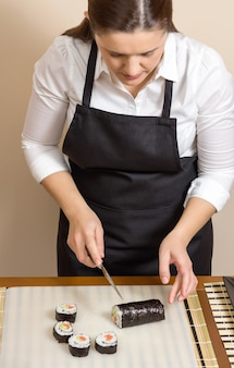 Portrait of woman chef cutting japanese sushi rolls with rice, avocado and shrimps on nori seaweed sheet
