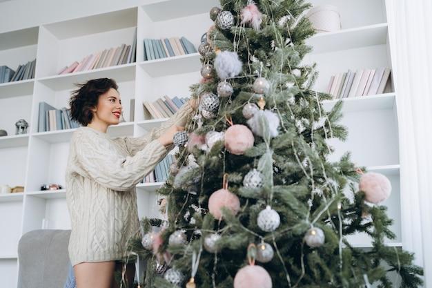 クリスマスツリーを飾る肖像画の女性