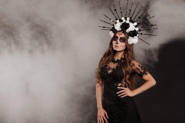 Portrait of woman at dia de los muertos sugar skull makeup isolatet background with smoke