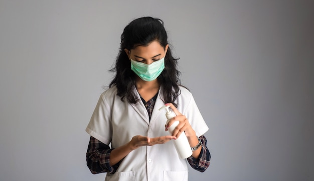 Portrait of woman doctor using a sanitizing gel from a bottle for hands cleaning.