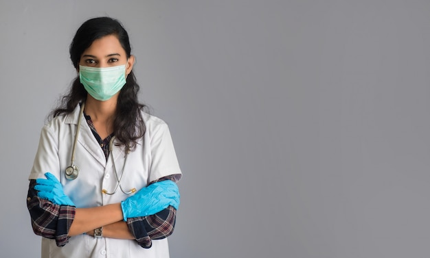 Portrait of woman doctor wearing a protective mask and gloves with a stethoscope. world epidemic of coronavirus concept.