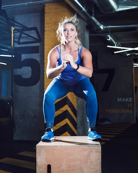 Portrait of a woman doing squat exercise on wooden box in fitness club