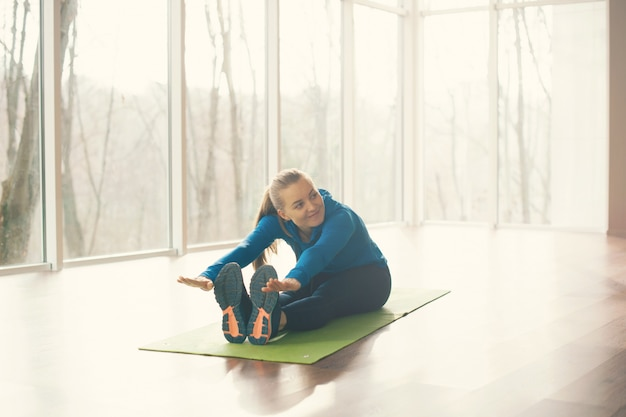 Portrait of woman doing stretching in studio during morning time
