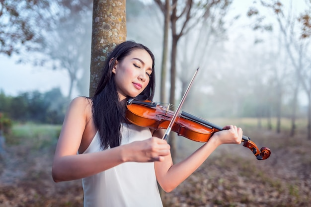 Portrait of woman dress in white long dress playing the violin, soft focus and vintage tone