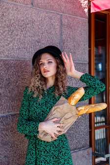 Portrait woman dressed in french style with baguette in hand. french style of paris. close-up of french woman in stylish clothes holding fresh baguettes and smiling. place for an inscription or logo