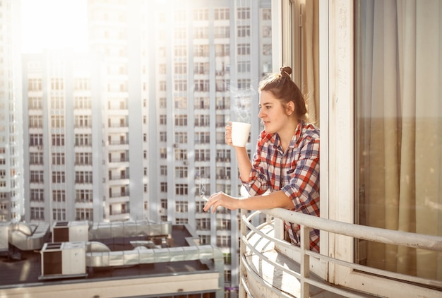 Portrait woman drinking coffee and smoking out of window