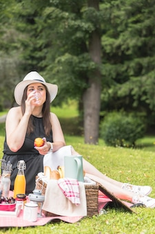 Portrait of woman drinking juice holding apple in hand on picnic