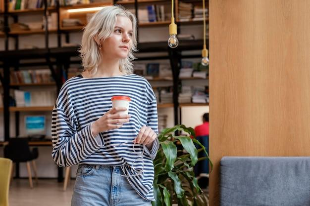Donna del ritratto che gode della tazza di caffè