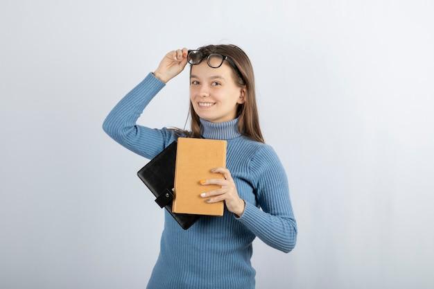 Ritratto di una donna in occhiali in possesso di due libri su sfondo bianco-grigio.
