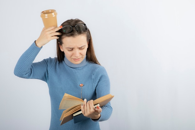 Ritratto di una donna con gli occhiali che legge un libro con una tazza di caffè.
