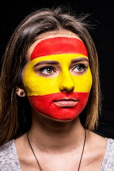 Portrait of woman face supporter fan of spain national team with painted flag face isolated on black background. fans emotions.
