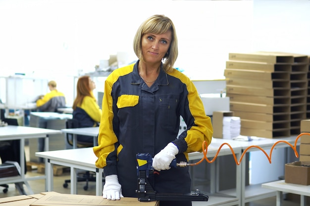 Portrait of woman factory worker standing near the production packaging line at plant for production of electrical products. in her hands packing the gun, stapler for packaging cartons