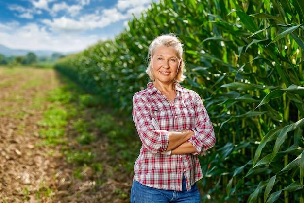 Portrait of a woman farmer in a cornfield.woman farmer harvesting corn.