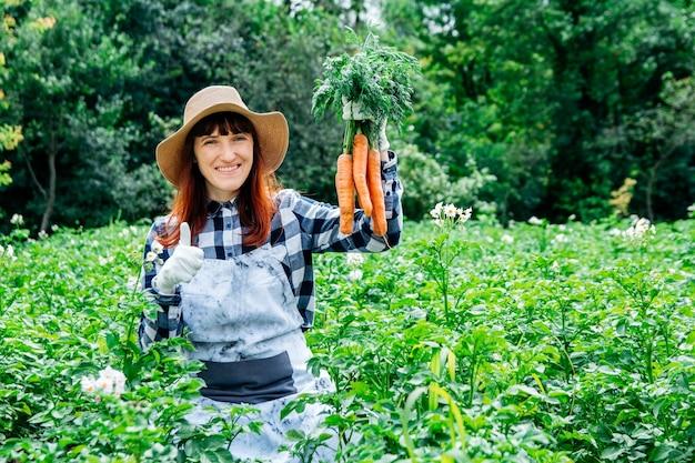 초상 여성 농부는 채소밭 배경에 있는 밀짚모자에 당근 다발을 들고 있다