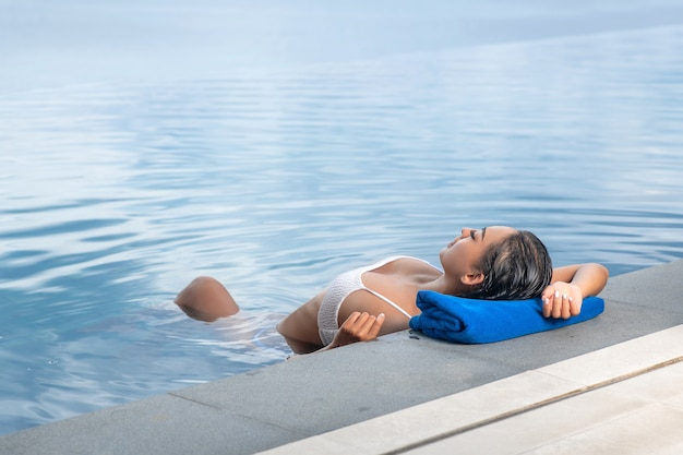 Portrait of a woman floating in the pool and resting her head on a towel.
