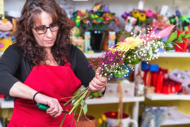 Portrait of woman florist wearing apron standing at counter making bouquet for client at flower shop.