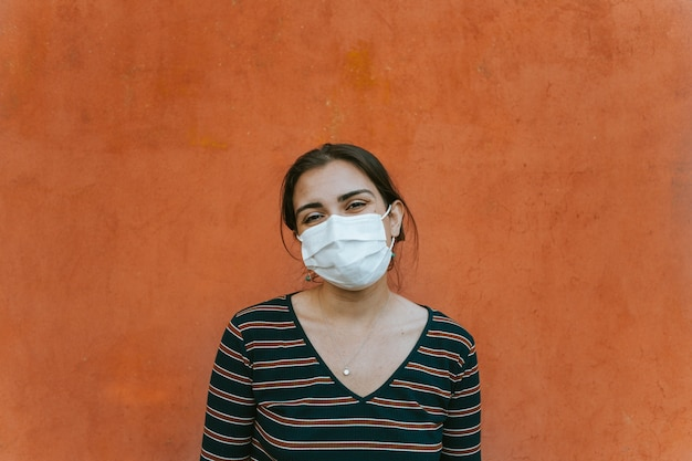 Portrait of a woman in front of a red wall smiling to camera while using a mask fro protection, happy and safeness concept