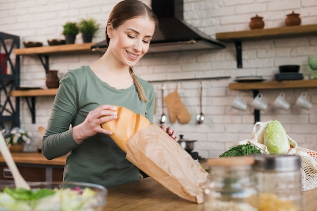 Portrait of woman getting bread out of bag