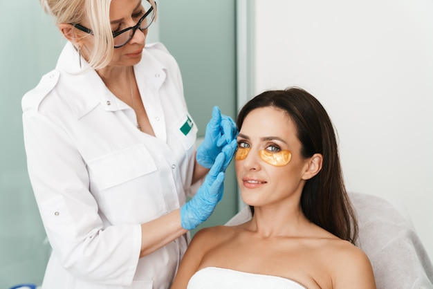 Portrait of woman getting cosmetic procedure with patches by specialist in beauty salon