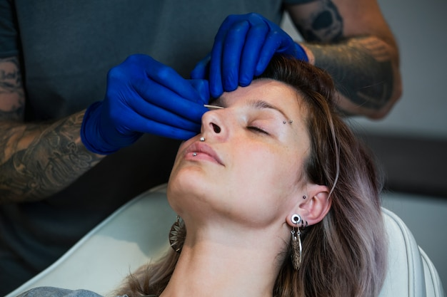 Portrait of a woman getting her nose pierced. nostril piercing procedure