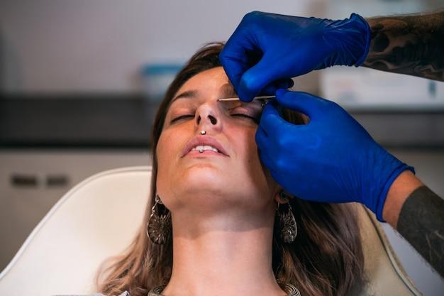 Portrait of a woman getting her nose pierced. nostril piercing procedure