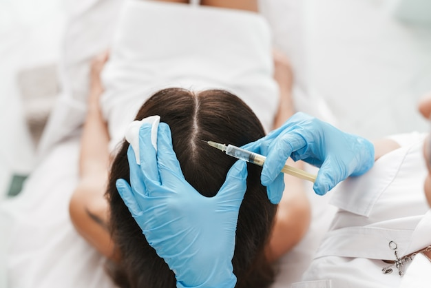 Portrait of woman getting mesotherapy treatment in head for stimulation of growing hair by specialist in beauty salon