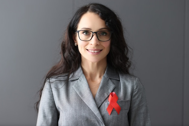 Portrait of woman in gray suit with a red ribbon on her chest fighting aids in the world