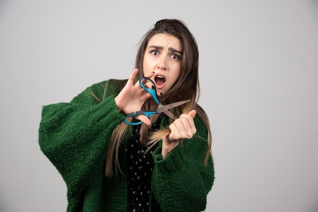 Portrait of woman in green jacket cutting her hair with scissors.