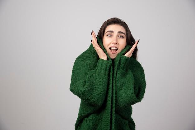 Portrait of woman in green jacket feeling happy.