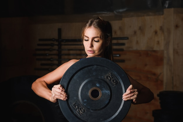 Portrait of woman in gym with plate 5 kg