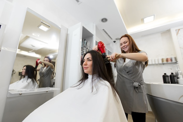 Portrait of a woman hairdresser who works with a client in a beauty salon. hairdresser dries wet hair girl with a hair dryer