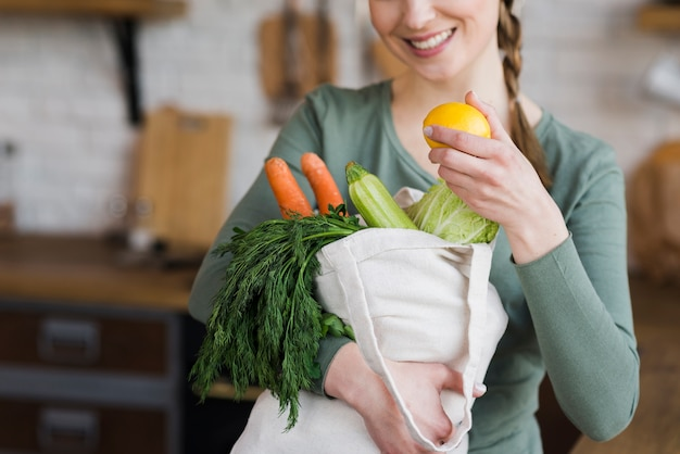 Portrait of woman holding bag with fresh vegetables