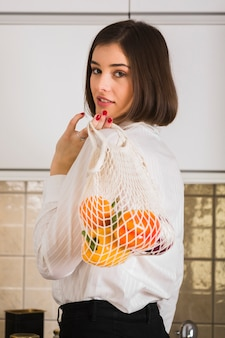 Portrait of woman holding bag with organic groceries