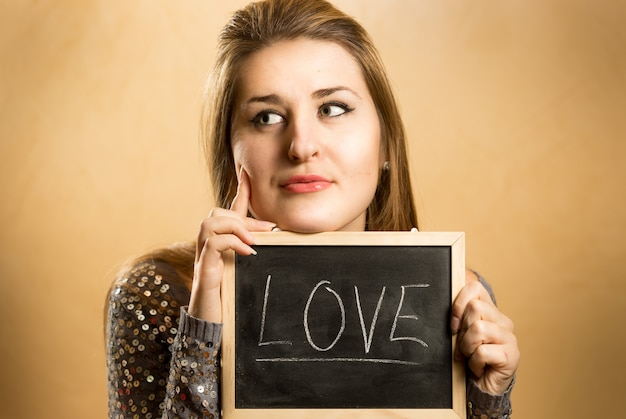 Portrait of woman holding blackboard and thinking of love