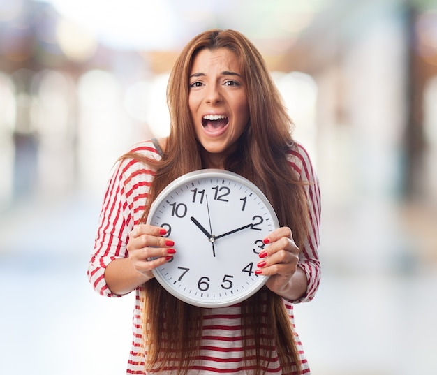 Portrait of woman holding clock and screaming