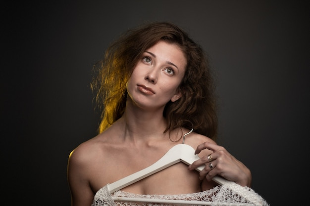 Ritratto di una donna che tiene un appendiabiti sotto le luci su uno sfondo scuro