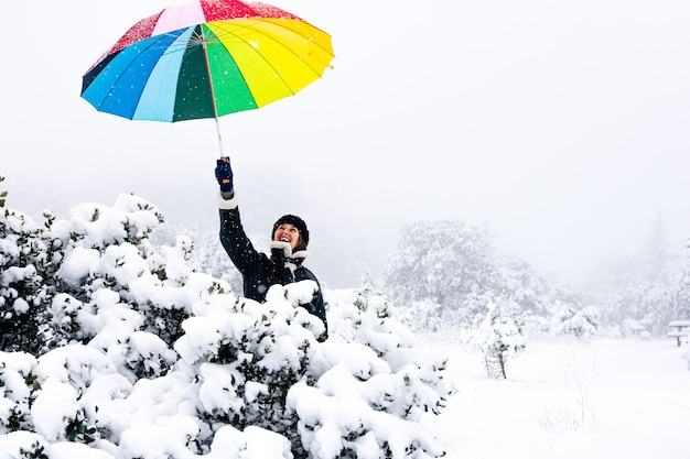 Portrait of a woman holding a colorful umbrella during a snowfall.