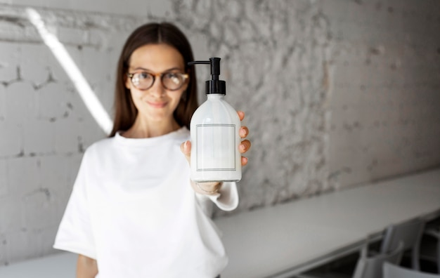 Portrait of woman holding disinfectant