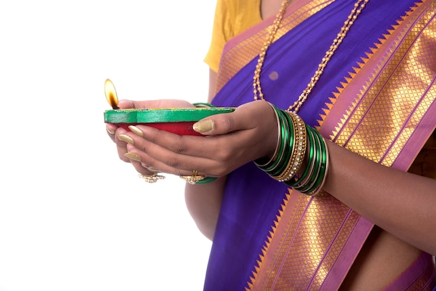 Portrait of a woman holding diya, diwali or deepavali photo with female hands holding oil lamp during festival of light on white wall
