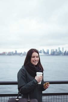 Portrait of woman holding food and drink while standing by railing