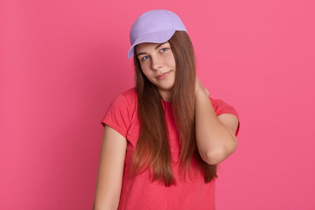 Portrait of woman holding her neck in discomfort against pink background, female with neck pain
