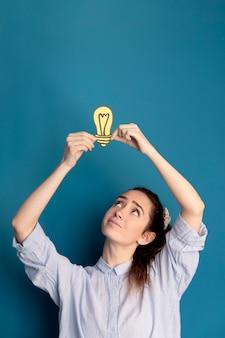 Portrait of woman holding idea light