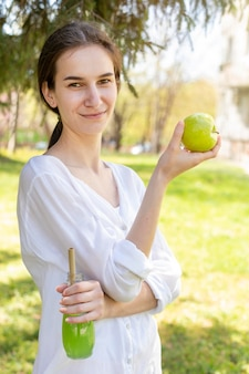 Portrait of woman holding juice bottle and apple
