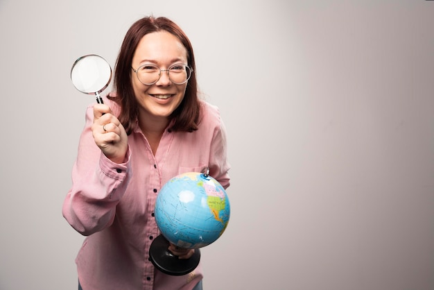 Portrait of woman holding a magnifying glass and earth globe. high quality photo
