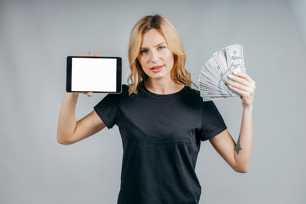 Portrait of a woman holding money and showing blank tablet computer screen