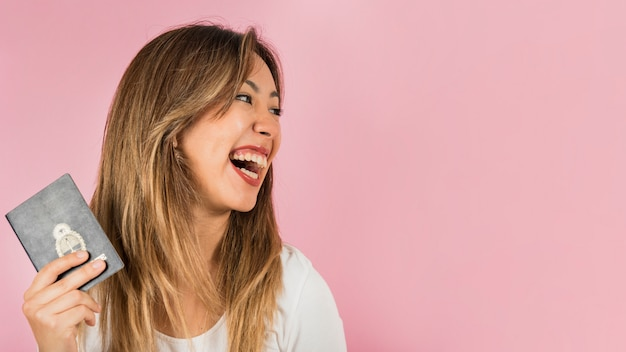 Portrait of a woman holding passport in her hand laughing against pink background