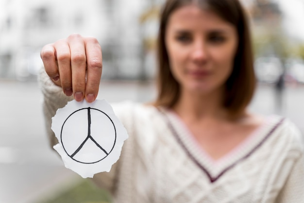 Portrait of a woman holding a peace sign